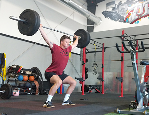 Young man lifting barbell over head